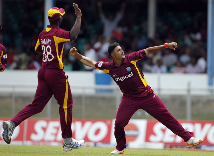 Ravi Rampaul celebrates with captain Darren Sammy after taking the wicket of Virat Kohli, who was caught behind for 2 runs, during their first One-Day International in Port of Spain, Trinidad. (AP Photo)