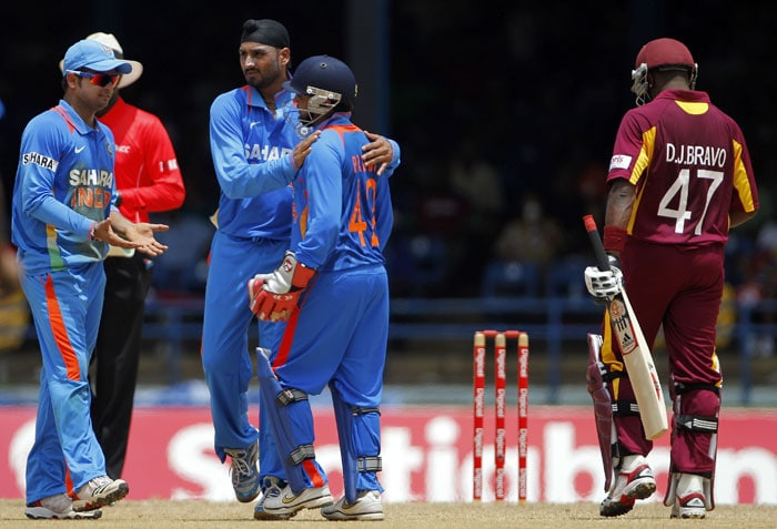 Parthiv Patel is congratulated by bowler Harbhajan Singh and captain Suresh Raina after his stumped out Dwayne Bravo during their first One-Day International in Port of Spain, Trinidad. (AP Photo)
