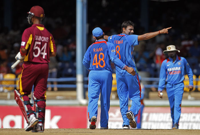 Praveen Kumar celebrates with his captain Suresh Raina after his teammate Harbhajan Singh took the catch to dismiss Lendl Simmons during their first One-Day International in Port of Spain, Trinidad. (AP Photo)