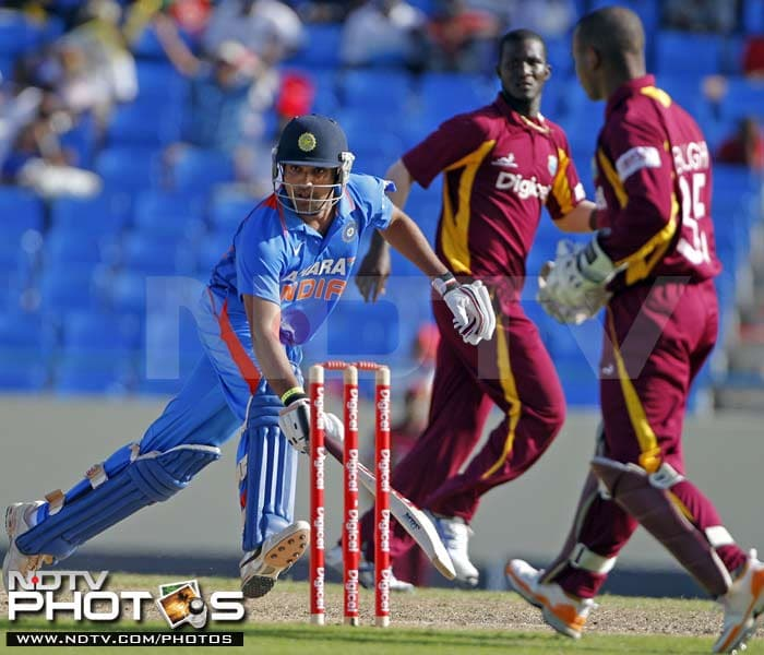 India's Rohit Sharma takes a run as West Indies' captain Darren Sammy and wicketkeeper Carlton Baugh look on during their third One-Day International in St. John's, Antigua. (AP Photo)