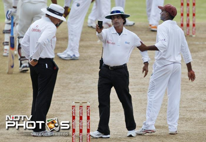 Umpire Asad Rauf uses a light meter to read the fading light following a rain delay, as the West Indies' Shivnarine Chanderpaul grabs his arm during the second day of the third Test match against India in Roseau, Dominica. At left is umpire Richard Kettleborough. (AP Photo)