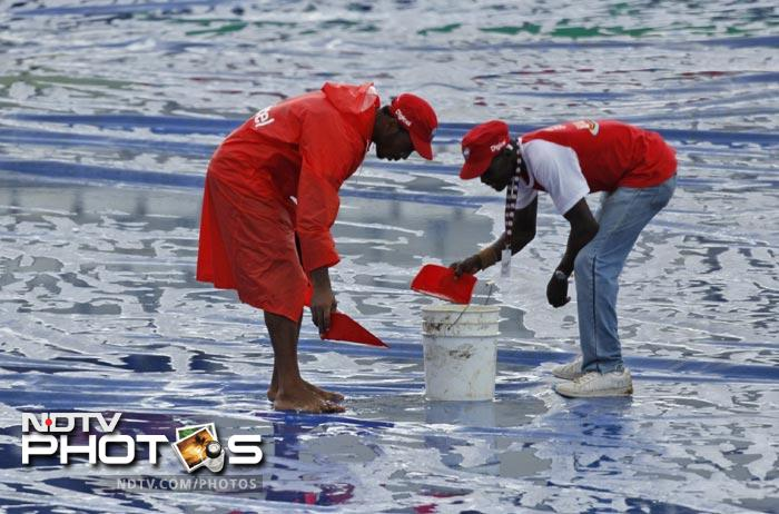 Grounds crew workers scoop rain water up from the tarp covering the pitch during a rain delay on the second day of the third Test match between the the West Indies and India in Roseau, Dominica. (AP Photo)