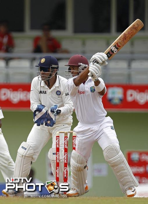 Carlton Baugh plays a shot for four runs as Mahendra Singh Dhoni looks on during the second day of the third Test match in Roseau, Dominica. (AP Photo)