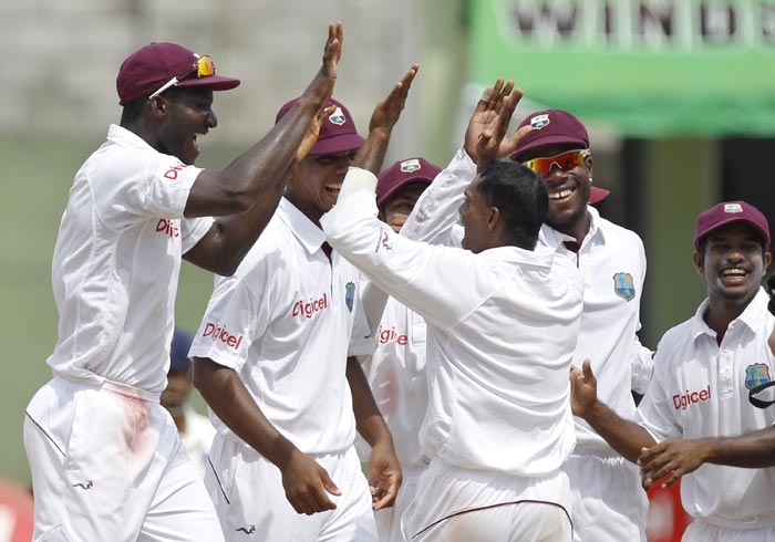 West Indies' Darren Sammy celebrates with Shivnarine Chanderpaul after he took the wicket of VVS Laxman, who was out stumped during the third day of the third Test match in Roseau, Dominica. (AP Photo)