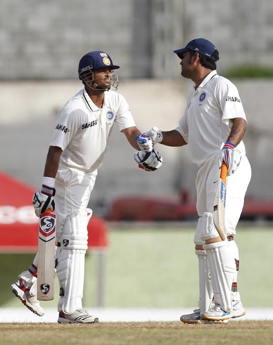 Suresh Raina is congratulated by Mahendra Singh Dhoni after scoring a half-century during the third day of the third Test match in Roseau, Dominica. (AP Photo)