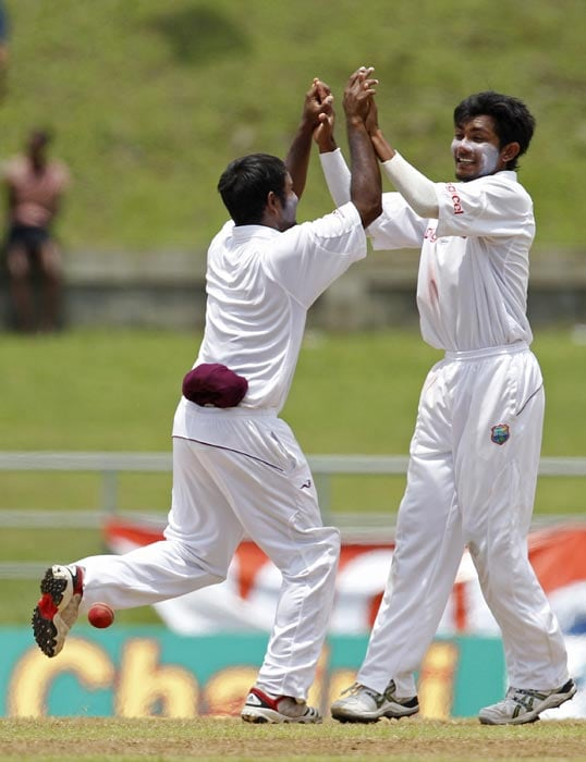 Devendra Bishoo celebrates with Adrian Barath after he caught Abhinav Mukund off the bowling of Bishoo on the third day of the third Test match in Roseau, Dominica. (AP Photo)