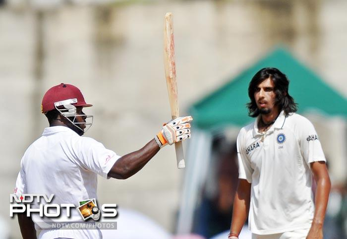 Kirk Edwards lifts his bat to acknowledge the cheering crowd after scoring half-century as Ishant Sharma looks on during the fourth day of third and final Test match between India and West Indies at the Windsor Park Stadium in Roseau, Dominica. (AFP Photo)