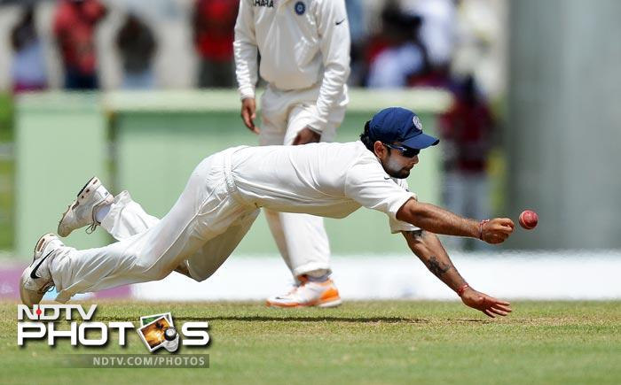 Virat Kohli dives to field a ball during the fourth day of third and final Test match between India and West Indies at the Windsor Park Stadium in Roseau, Dominica. (AFP Photo)