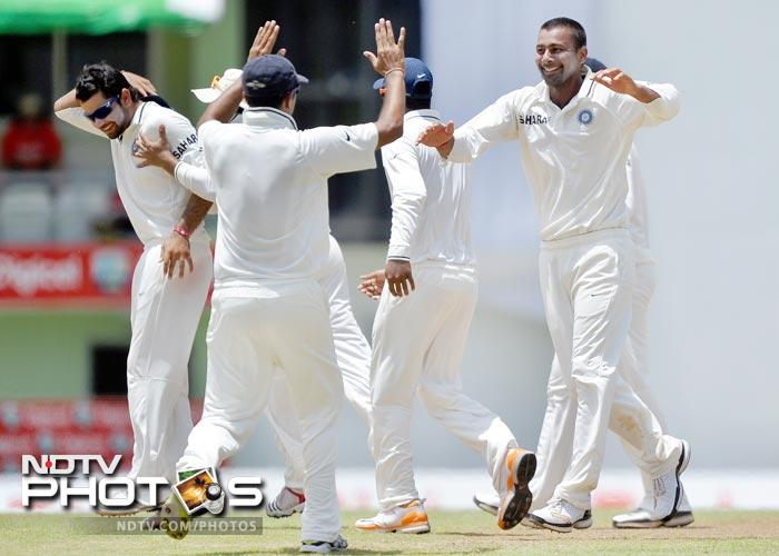 Praveen Kumar and his teammates celebrate dismissing Adrian Barath during the fourth day of third and final Test match between India and West Indies at the Windsor Park Stadium in Roseau, Dominica. (AFP Photo)