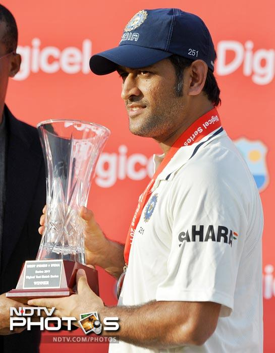 Indian captain Mahendra Singh Dhoni receives the series winning trophy at the end of the third and final Test match between India and West Indies at the Windsor Park Stadium in Roseau, Dominica. India won the three-match Test series 1-0 following a 63-run victory inside four days in the first Test and drawn the last two. (AFP Photo)