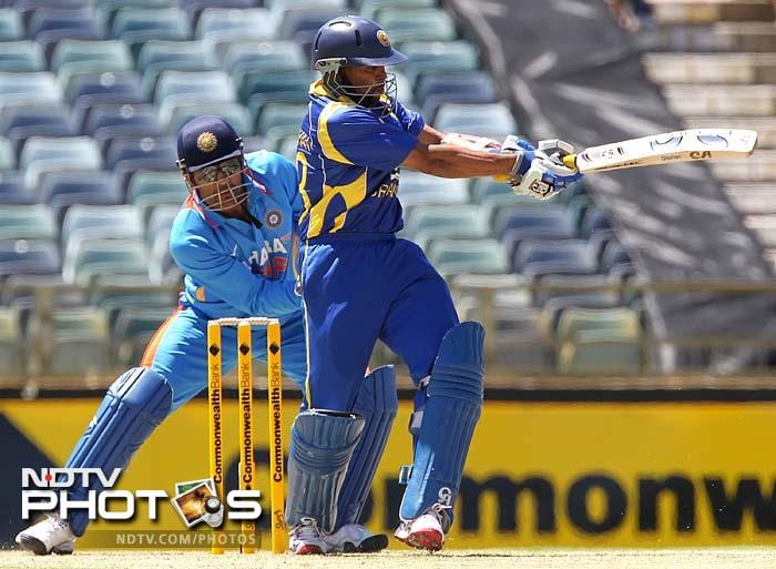 Sri Lankan opening batsman Tillakaratne Dilshan (R) pulls to the boundary watched by Indian wicketkeeper and captain MS Dhoni (L). Dilshan scored 48 off 79 balls.