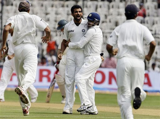 Indian players run in to congratulate bowler Zaheer Khan after he took the wicket of Matthew Hayden on the first day of the first Test between India and Australia in Bangalore.