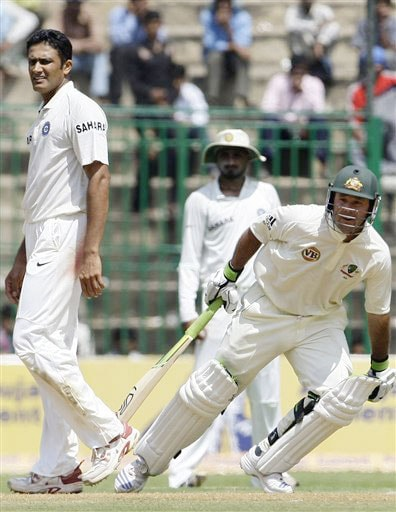 Ricky Ponting scores a run as Anil Kumble and Harbhajan Singh look on during the first day of the first Test between India and Australia in Bangalore.