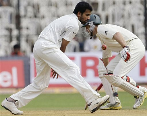 Zaheer Khan fields off his own bowling as Simon Katich takes evasive action on the first day of their first Test in Bangalore.
