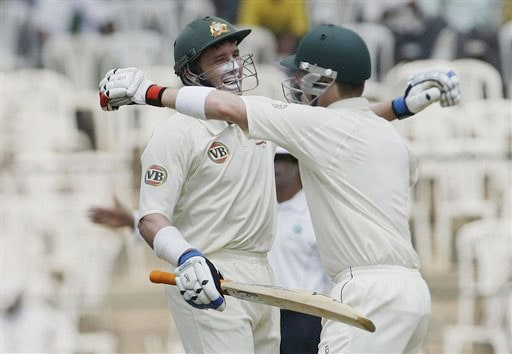 Mike Hussey is congratulated by teammate Brad Haddin after he scored a century on the second day of the first Test match between India and Australia in Bangalore.