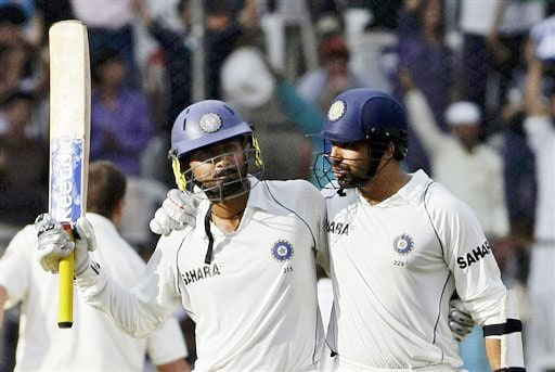 Harbhajan Singh raises his bat to acknowledge the crowd's applause after he scored fifty runs, as teammate Zaheer Khan congratulates him on the third day of the first Test in Bangalore.