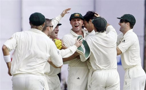 Australian players celebrate with Matthew Hayden after he took a catch to dismiss Virender Sehwag on the third day of the first Test in Bangalore.