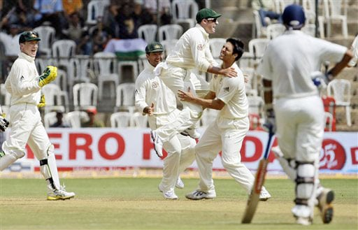 Australian players celebrate with Mitchell Johnson after he dismissed Sachin Tendulkar Rahul Dravid looks on during the third day of the first Test in Bangalore.