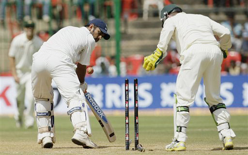 Mahendra Singh Dhoni looks back as he is clean-bowled by Michael Clarke as wicketkeeper Brad Haddin looks on during the third day of the first Test in Bangalore.