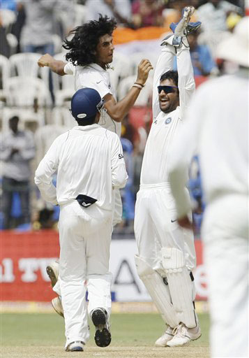 Ishant Sharma is congratulated by Mahendra Singh Dhoni after he took the wicket of Ricky Ponting on the fourth day of the first Test between India and Australia in Bangalore.