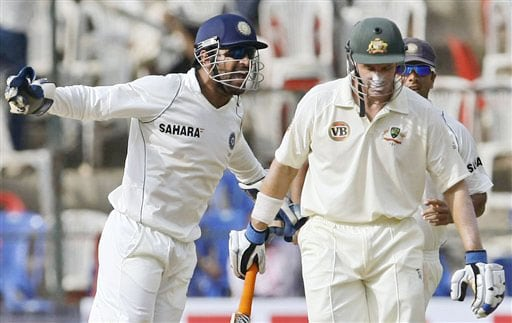 Mahendra Dhoni and Rahul Dravid react after Mike Hussey was clean bowled by Harbhajan Singhon the fourth day of the first Test between India and Australia in Bangalore.