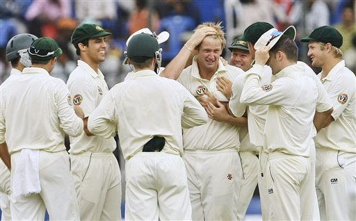 Australian players congratulate bowler Cameron White after he took the wicket of Sachin Tendulkar on the final day of the first Test match between India and Australia in Bangalore.