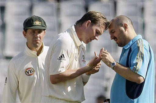 Brett Lee is attended to by team physiotherapist Alex Kontouris as Ricky Ponting looks on on the second day of their second Test against India in Mohali.