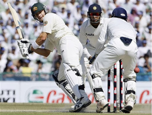 Shane Watson plays a shot as VVS Laxman and Mahendra Singh Dhoni look on during the third day of the second Test between India and Australia in Mohali.