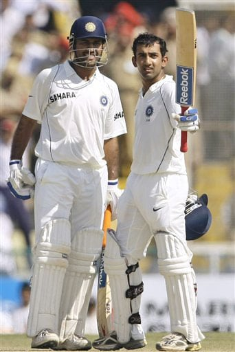 Gautam Gambhir raises his bat to acknowledge applause from the crowd after he scored a century as captain Mahendra Singh Dhoni looks on during the fourth day of the second Test between India and Australia in Mohali.