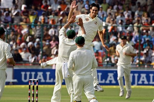 Mitchell Johnson celebrates with teammates after dismissing Sachin Tendulkar during the first day of their third cricket Test match in New Delhi on Wednesday, October, 2008.