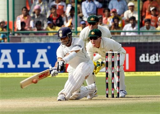 Sachin Tendulkar, left, hits a shot as Australian wicketkeeper Brad Haddin and Matthew Hayden, back, look on during the first day of their third cricket Test match in New Delhi on Wednesday, October, 2008.