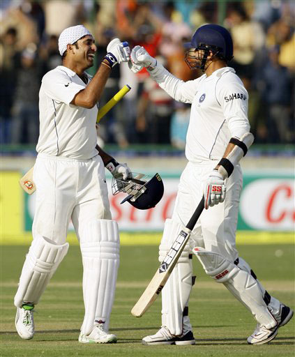 VVS Laxman and Zaheer Khan celebrate after Khan got his second century and India declared their inning on the second day of the third Test between India and Australia in New Delhi.