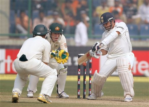 Sachin Tendulkar (right) takes position to play a square cut on the final day of the third Test cricket match between India and Australia in New Delhi on Sunday, Nov. 2, 2008.