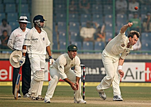 Brett Lee, right, bowls as Australian cricket team captain Ricky Ponting, second right, and Indian batsman Gautam Gambhir, second right, watch on the final day of the third Test cricket match between India and Australia in New Delhi on Sunday, Nov. 2, 2008.