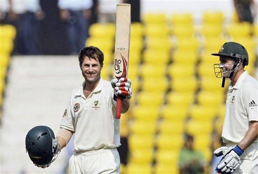 Simon Katich raises his bat after he scored a century as teammate Mike Hussey looks on during the third day of the Nagpur Test. (AP Photo)