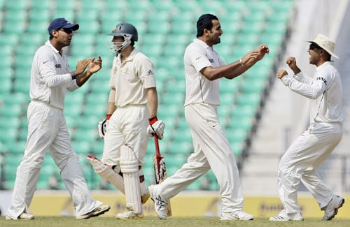 M. Vijay and Virender Sehwag run in to congratulate teammate Zaheer Khan for the dismissal of Simon Katich during the third day of the Nagpur Test. (AP Photo)