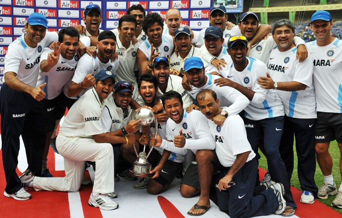 An elated Indian team poses with the Border-Gavaskar Trophy after beating Australia by 7 wickets in the second Test in Bangalore. India clinched the series 2-0.
