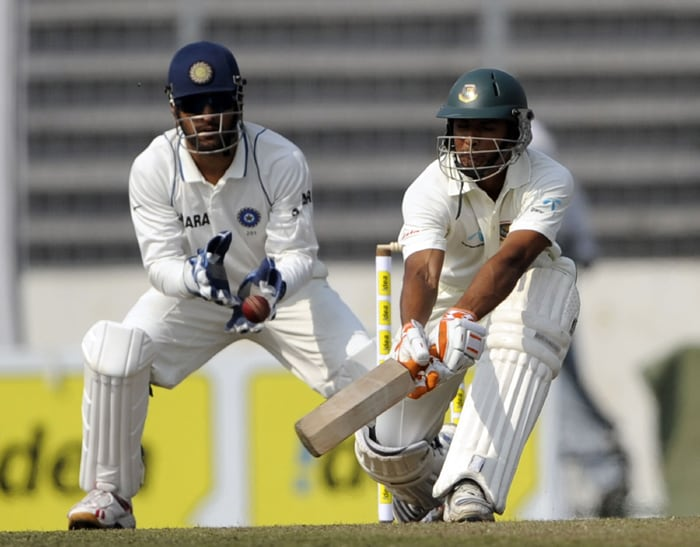 Bangladeshi cricketer Mahmudullah Riyad plays a shot enroute to his 96* as Indian cricket team captain Mahendra Singh Dhoni looks on during the first day of the second Test. (AFP Photo)