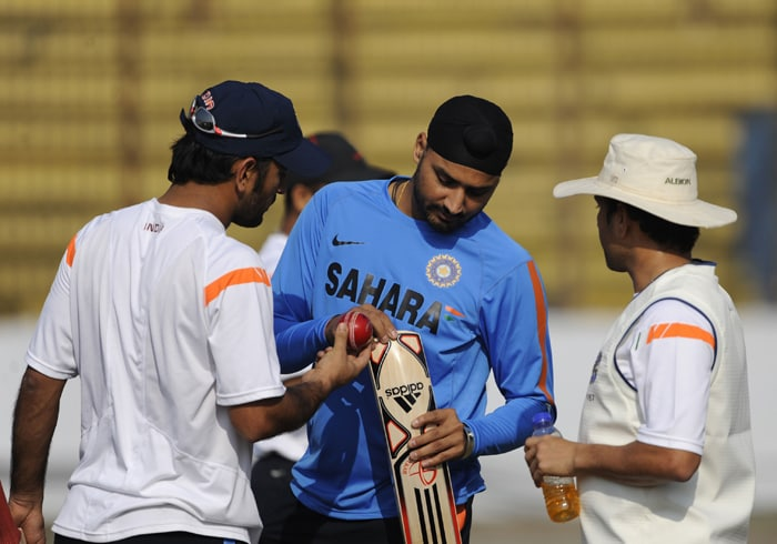 MS Dhoni (L) and his teammates Sachin Tendulkar (R) and Harbhajan Singh (C) inspect a bat during a practice session at Zohur Ahmed Chowdhury Stadium in Chittagong. India will play two Tests against Bangladesh. Dhoni has been ruled out of the first Test due to a back spasm. (AFP PHOTO)