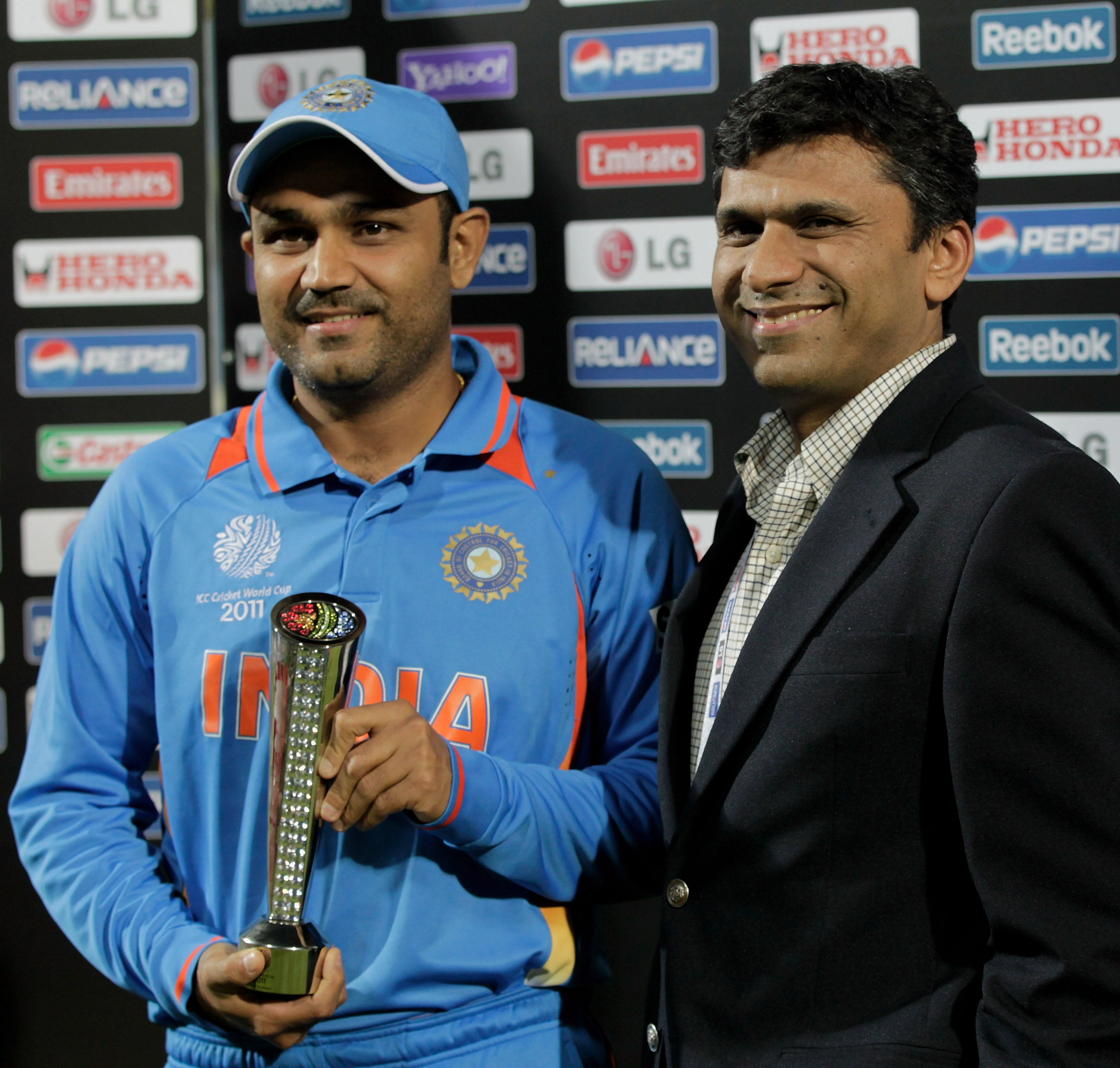 Virender Sehwag holds the Man Of The Match trophy with the CEO of Coca Cola for India during the opening game of the ICC World Cup between Bangladesh and India at the Sher-e-Bangla National Stadium in Dhaka, Bangladesh. (Getty Images)