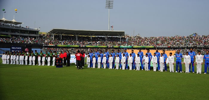 The Bangladeshi (In Green) and Indian (In Blue) teams line up for the national anthems ahead of the start of the first match in the ICC World Cup at the Sher-e Bangla National Stadium in Dhaka. (AFP Photo)