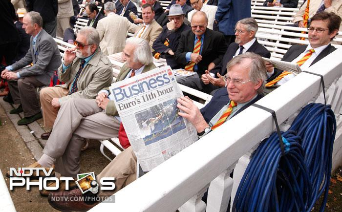 A member of the MCC reads the business section of a British daily newspaper as he waits for the start of play in the England verses India Test on the first day of the first Test match at the Lord's Cricket ground in London. (AP Photo)