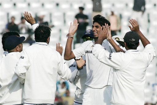 Ishant Sharma and teammates celebrate dismissal of Alastair Cook during fifth and final day of second Test between India and England in Mohali.