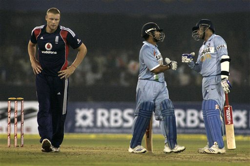 Virender Sehwag and Sachin Tendulkar greet each other after scoring a boundary as England bowler Andrew Flintoff looks on during the fifth One-Day International match between India and England in Cuttack. (AP Photo)