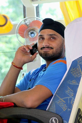 Harbhajan Singh talks on the phone in the team bus while leaving for the team's fitness and conditioning camp, ahead of tri-series in Sri Lanka and Champions Trophy, in Bangalore. (PTI Photo)