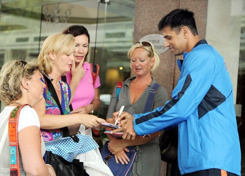 Rahul Dravid signs autograph for fans as he leaves for team's fitness and conditioning camp, ahead of tri-series in Sri Lanka and Champions Trophy, in Bangalore. (PTI Photo)