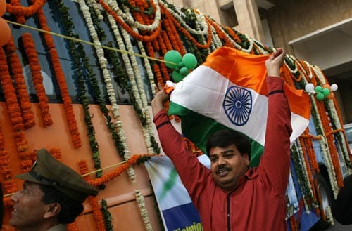 An Indian supporter waves the national flag as cricketers journey from a hotel in a garlanded bus towards a welcome ceremony in New Delhi on March 6, 2008.