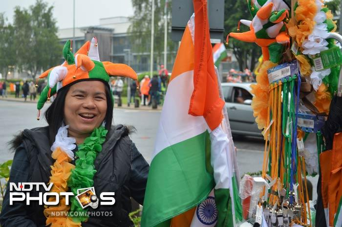 An Indian fan with the traditional tricolour garland, standing next to a souvenir seller outside the Swalec Stadium in Cardiff.