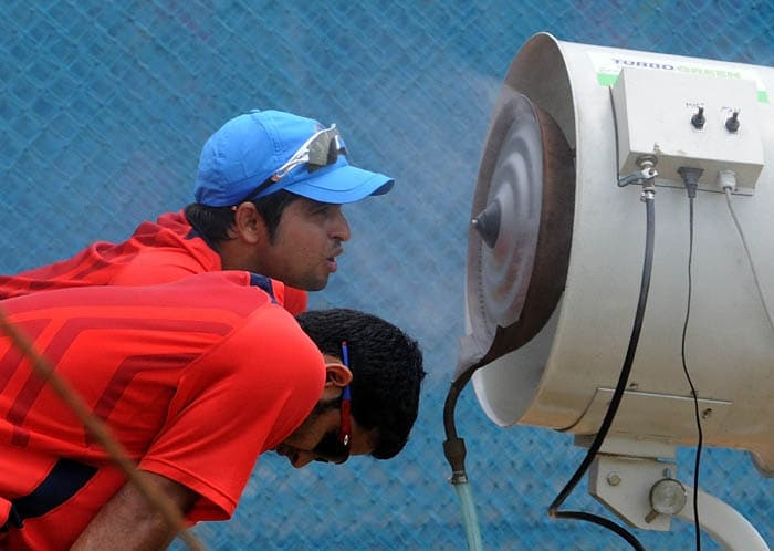 Indian cricketers Piyush Chwla and Suresh Raina cool down as they stand in front of water coolers during a training session. (AFP Photo)