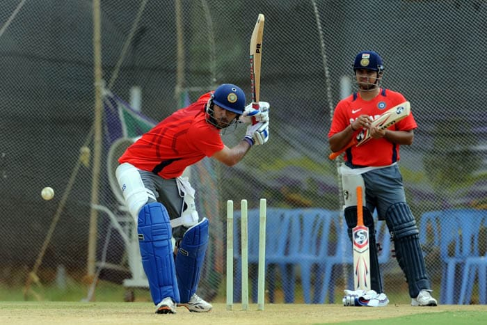India batsman Yuvraj Singh plays a shot in the nets as Suresh Raina waits for his turn to bat during a training session. (AFP Photo)